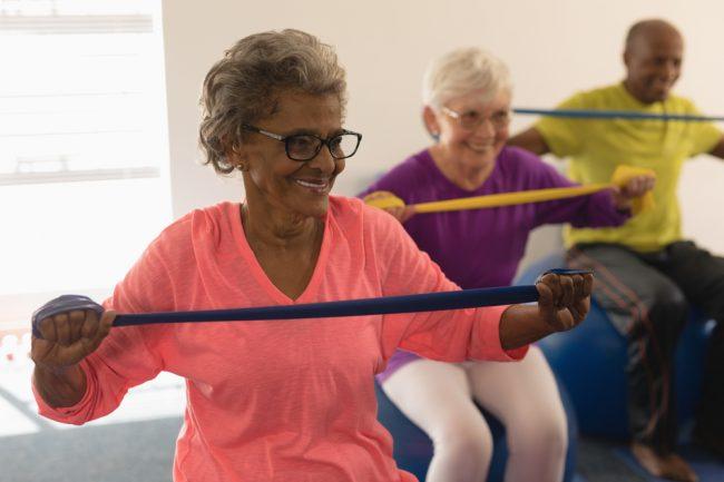 mulher de idade se exercitando com elástico de resistência