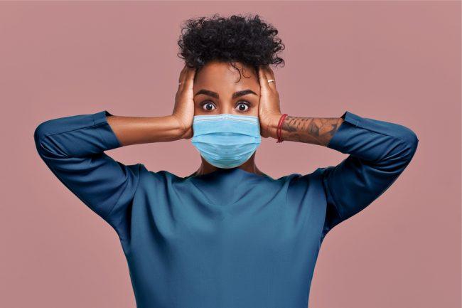 mulher jovem negra com máscara e as mãos no rosto