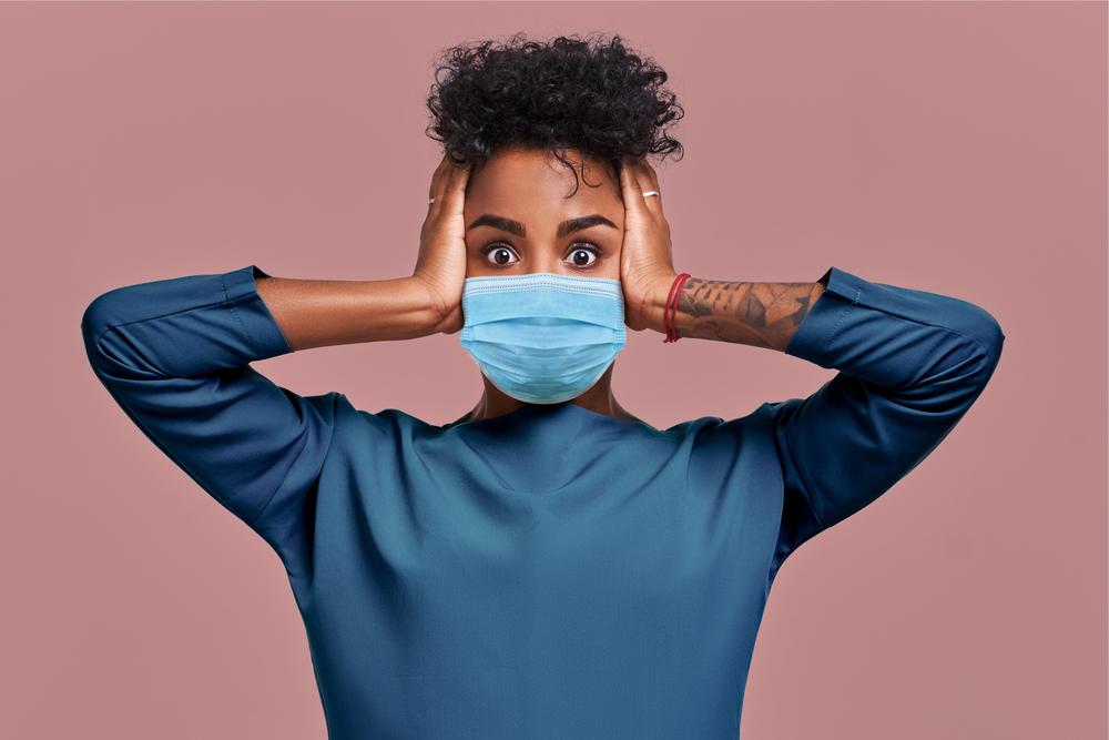 mulher negra usando máscara com as mãos na cabeça