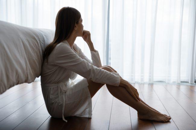 mulher sentada no chão ao lado da cama