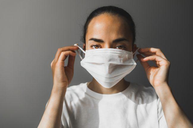 Mulher colocando máscara branca no rosto