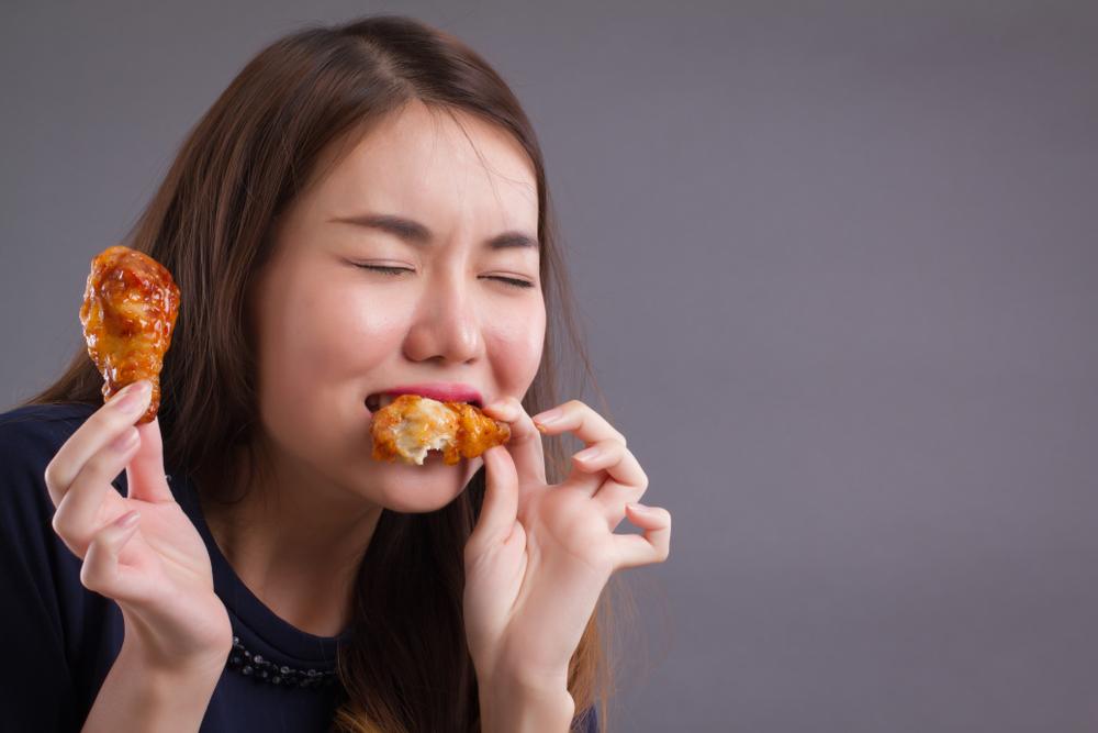 Mulher oriental comendo coxa de frango com ketchup