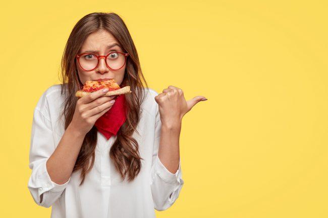 mulher jovem mordendo pedaço de pizza