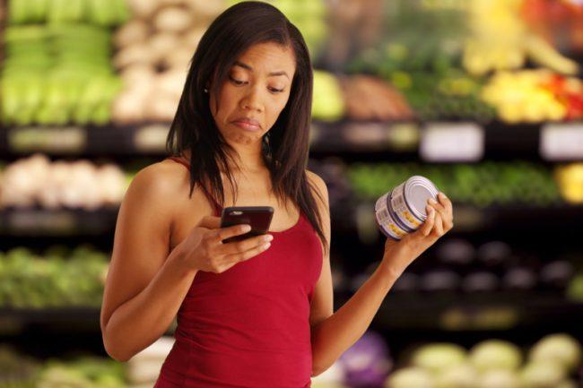 mulher negra lendo rótulos no mercado