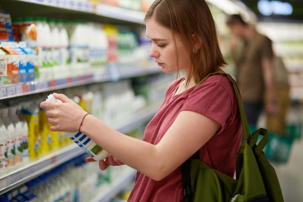 mulher no supermercado lendo rótulo do leite