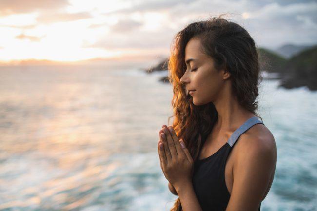 Mulher orando com pôr-do-sol ao lado