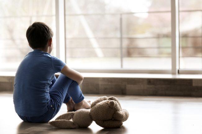 Menino triste sentado no chão ao lado de um ursinho de pelúcia