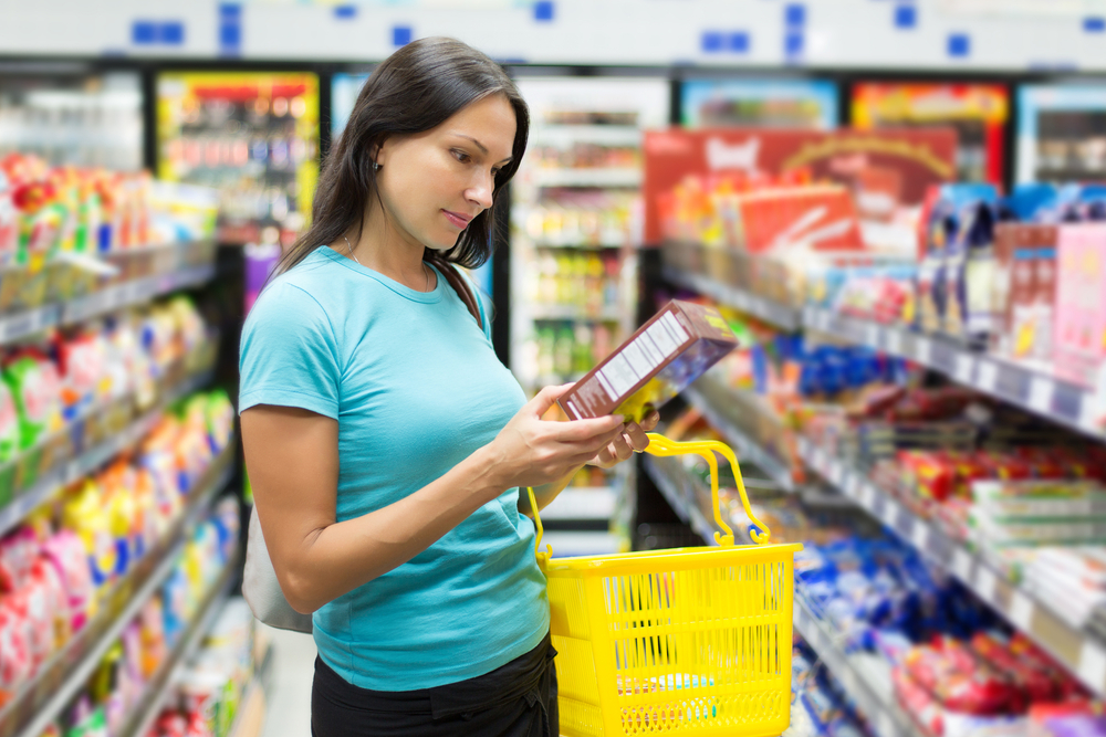 mulher no mercado lendo rótulo de produto