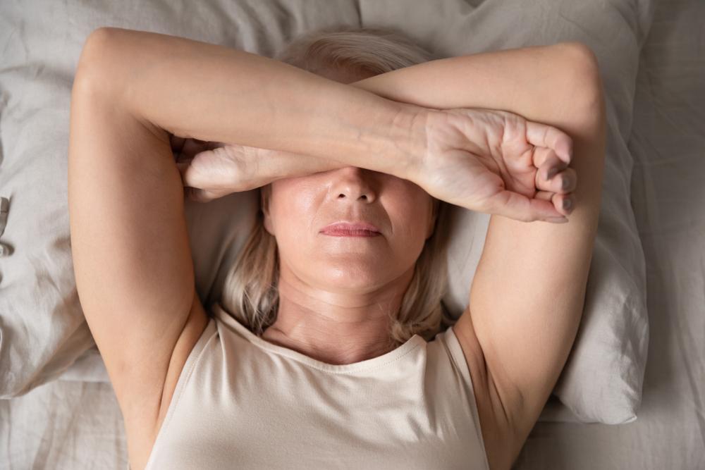 Mulher deitada na cama com os braços sobre o rosto.