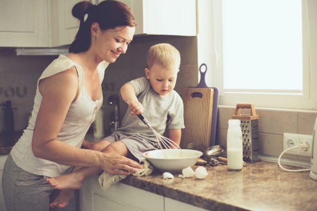 mãe e filho bebê batendo ovos na cozinha