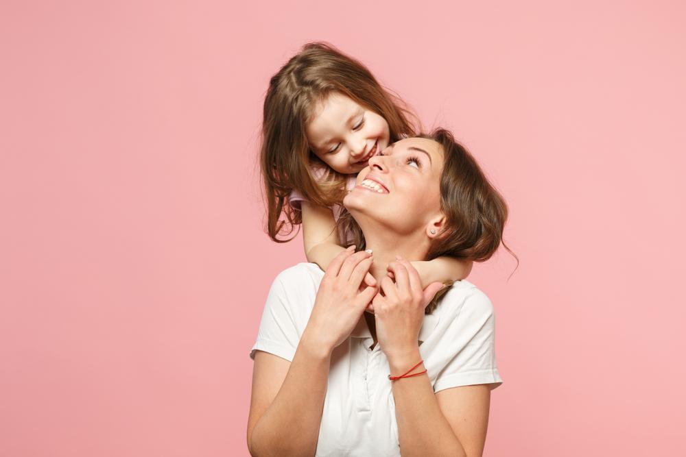 mãe jovem e filha criança se abraçando