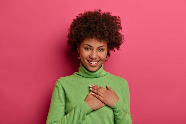 mulher afrodescendente sorrindo com a mão no coração