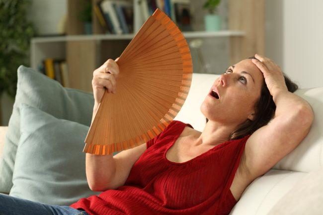 Mulher no sofá se abanando com leque