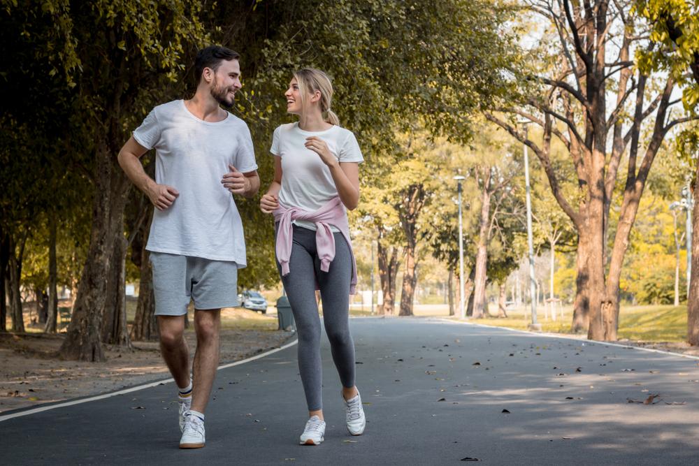 Casal fazendo caminhada em um parque
