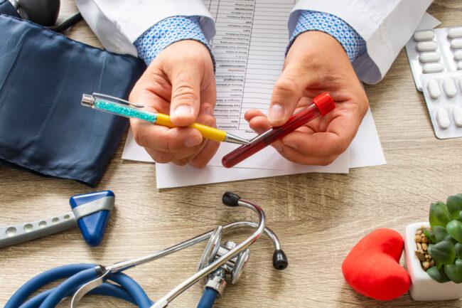 médico segurando um tubete de sangue