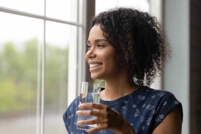 mulher olhando pela janela com um copo de água na mão