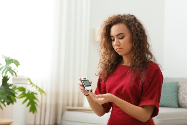 menina jovem medindo glicemia