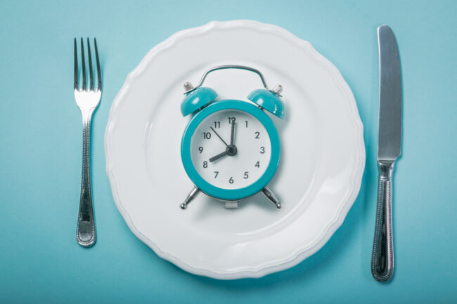 relógio dentro do prato junto com os talheres